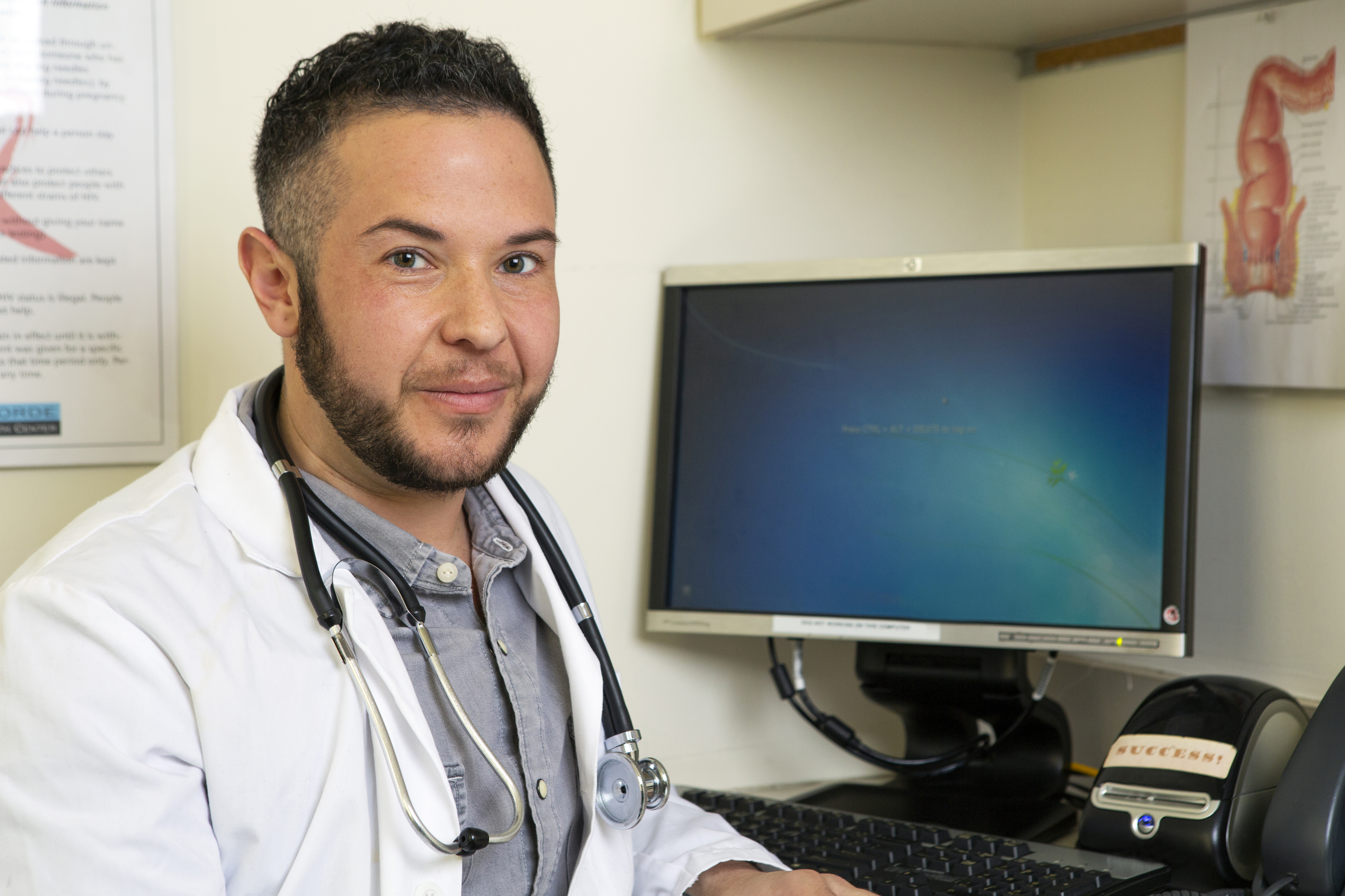 A transmasculine doctor with his computer.