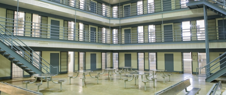 The central area of a prison, showing several metal tables and three floors of cells.