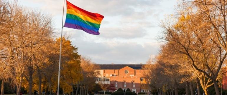 A rainbow flag flies outside of a school building (Photo Credit: Megan Long Photography)