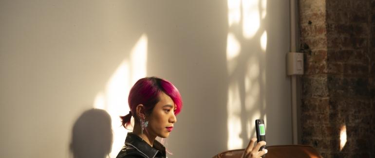 A non-binary femme using their phone