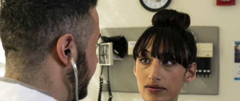 PHOTO: A transgender woman in a hospital gown listens as a doctor speaks