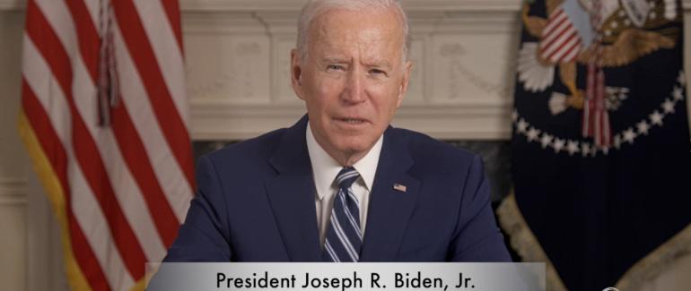 President Biden sitting at desk with digital banner showing he/him pronouns