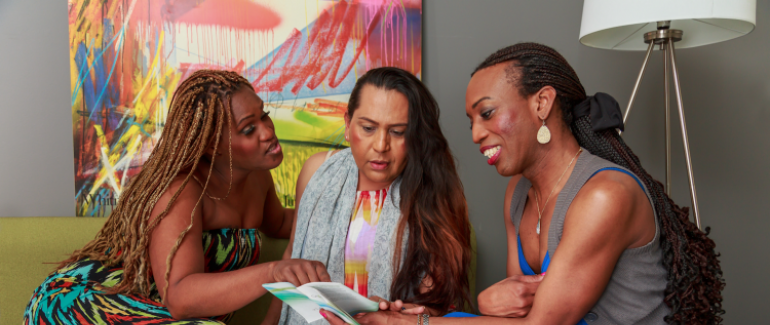 Three trans women sitting and reading a booklet