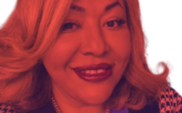 A headshot of Ruby Corado, smiling. with the phrase RUBY CORADO Community Builder Honoree