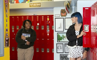 Two non-binary students looking at eachother in a school hallway