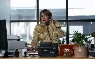 A transfeminine executive using the phone in her office with a pen