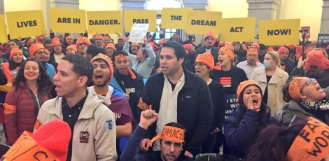 "A crowd of protesters, many wearing orange hats and headbands, in the rotunda of the U.S. Capitol. Protesters in the back hold up signs saying ""Our lives are in danger. Pass the Dream Act now!"""